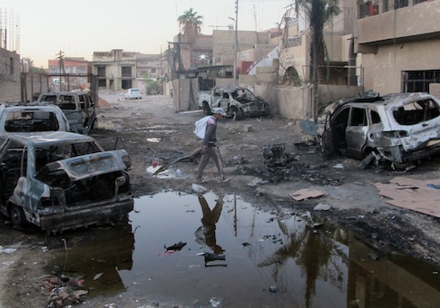 An Iraqi man inspects the aftermath of a bombing in the Baghdad al-Jadidah district