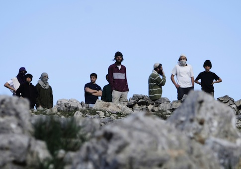 Israeli settlers of Yitzhar take position during a confrontation with Palestinians