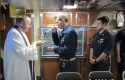 A catholic Navy chaplain gives communion to a L.T. j.g. / AP