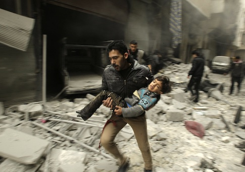 A man runs as he carries a child who survived from what activists say was an airstrike by forces loyal to Syrian President Bashar al-Assad