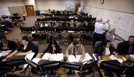 A roomful of people work to process applications for Cover Oregon (AP)