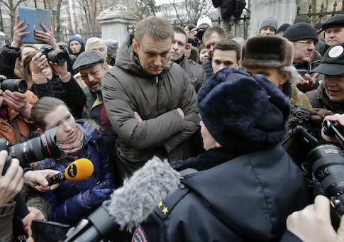 Opposition leader Navalny speaks to a police officer outside a courthouse in Moscow