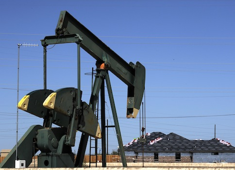 A pump jack works beside the site of new home construction, in Midland, Texas / AP