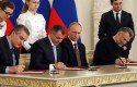 Russian President Vladimir Putin looks on as Crimean leaders signing a treaty to incorporate Crimea into Russia / AP