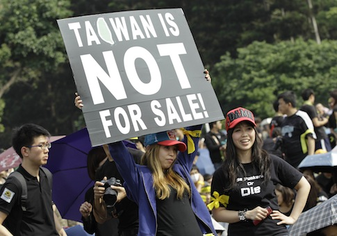 Protesters display a banner denouncing the controversial China Taiwan trade pact / AP