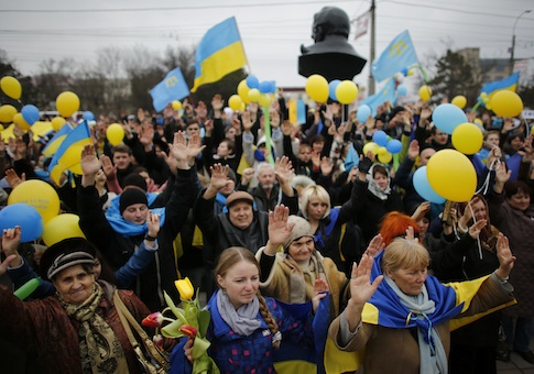 Pro-Ukrainian supporters raise their hands as they take part in a rally in Simferopol