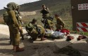 A wounded Israeli soldier is treated in the Golan Heights, Tuesday, March 18, 2014