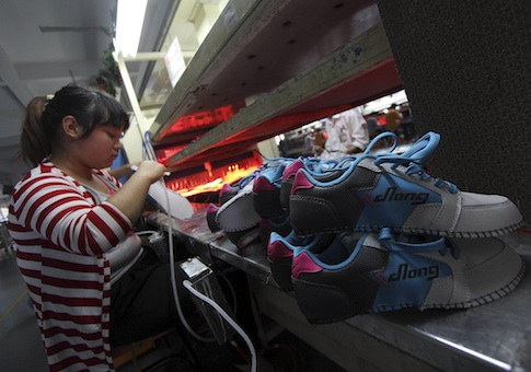 A Chinese worker labors in a factory making sports shoes