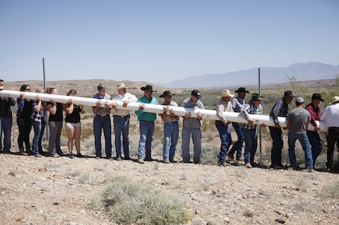 Cliven Bundy supporters raise a banner during a rally / AP