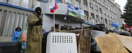 A pro-Russian protester gestures as he stands guard at a barricade in front of the seized office of the SBU state security service in Luhansk