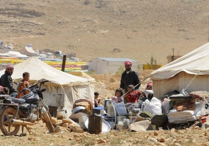 Refugees who fled the violence from the Syrian town of Flita, near Yabroud, stand outside their tents at the border town of Arsal