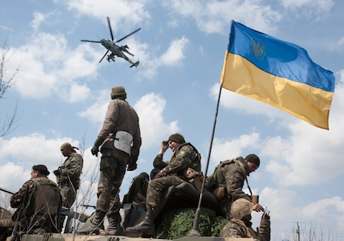 A military Ukrainian Army helicopter flies over a column of Ukrainian Army combat vehicles