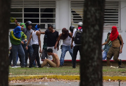 Government supporters beat a naked opposition student / AP