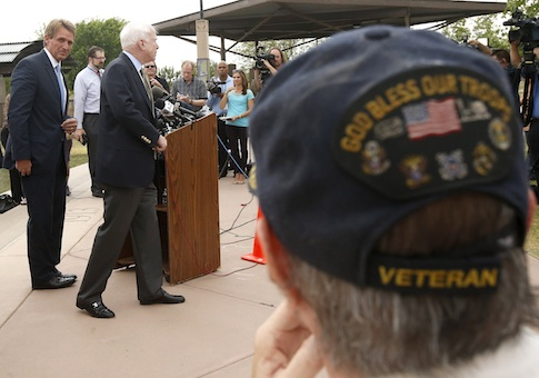 With Vietnam military veteran Chuck Tharp, right, listening in, Sen. John McCain, second from left, R-AZ, and Sen. Jeff Flake, left, R-AZ, finish up a news conference to discuss recent reports that dozens of VA hospital patients in Arizona may have died while awaiting medical care in the Phoenix VA Health Care System