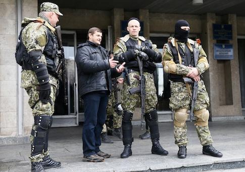 A local resident talks to pro-Russian armed men standing guard outside the mayor's office in Slaviansk