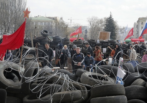 People stand at a barricade at the regional administration building that they had seized earlier in Donetsk