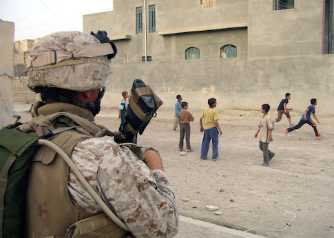 A U.S. marine observe children play in Ramadi / AP