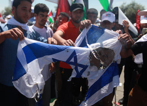 Palestinian youth burn an Israeli flag. / AP