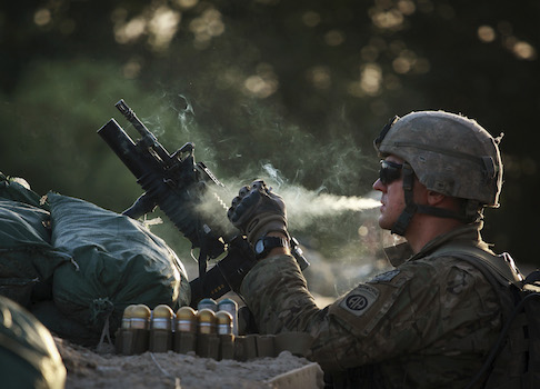 A U.S. Army soldier smokes a cigarette while on guard duty in Iraq / AP