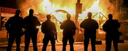 Pro-Russian separatists pose in front of a burning shop in Ukraine / AP