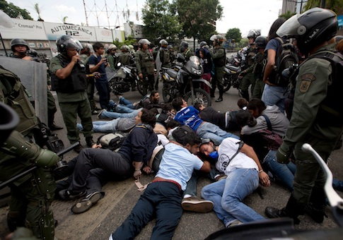 Bolivarian National Guardsmen surround a group of anti-government demonstrators