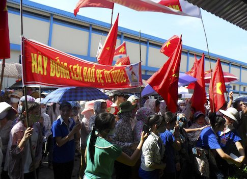 Workers wave Vietnamese national flags during an anti-China protest / REUTERS