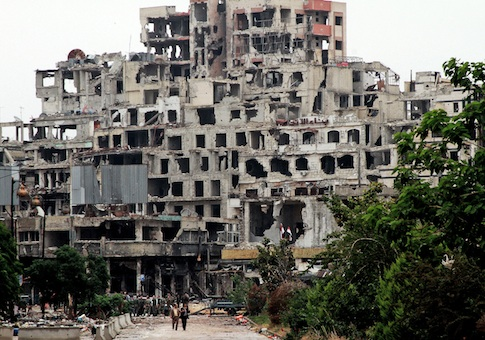 Syrian government officials walk on a road, back dropped, by damaged buildings from fighting with Free Syrian Army fighters in the old city of Homs, Syria