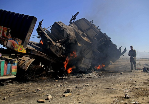 An Afghan policeman stands near a burning NATO supply truck in Behsud district of Jalalabad east of Kabul, Afghanistan