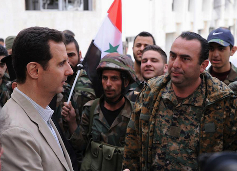 Syrian President Bashar Assad, left, talks to government soldiers / AP