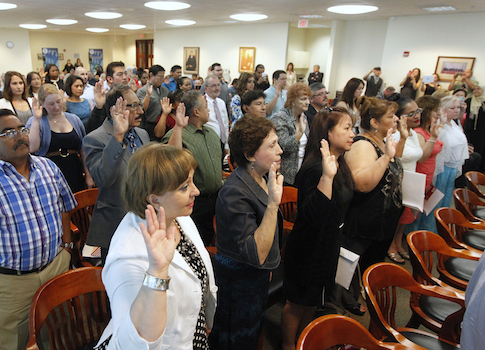 Participants take the oath of citizenship to become U.S. citizens during the first of two naturalization ceremonies / AP