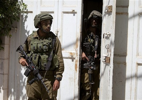 Israeli soldiers search a house looking for three missing Israeli teenagers / AP