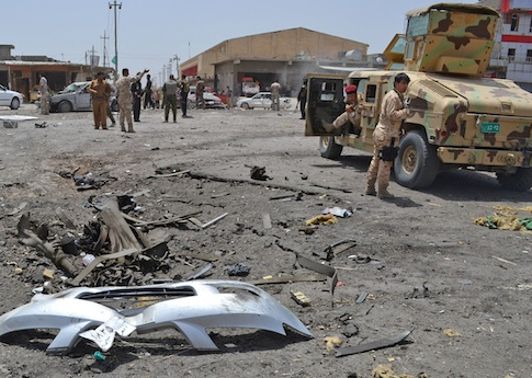 Civilians and security forces inspect the site of a suicide bomb attack in Tuz Khormato, 130 miles north of Baghdad, Iraq