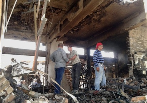 People inspect buildings damaged by an Iraqi government airstrike on the Islamic State in Iraq and the Levant controlled city of Mosul