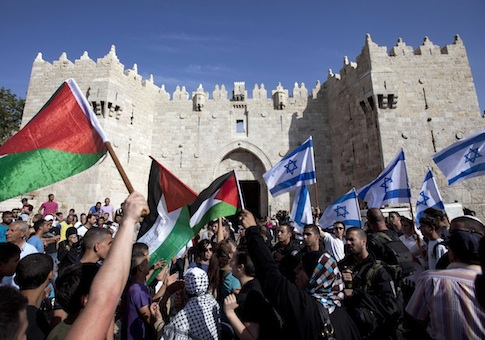 Israelis and Palestinians wave flags as Israelis march celebrating Jerusalem Day outside Damascus Gate in Jerusalem's old city