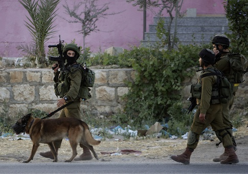 Israeli soldiers walk during an operation in search of kidnapped teenagers