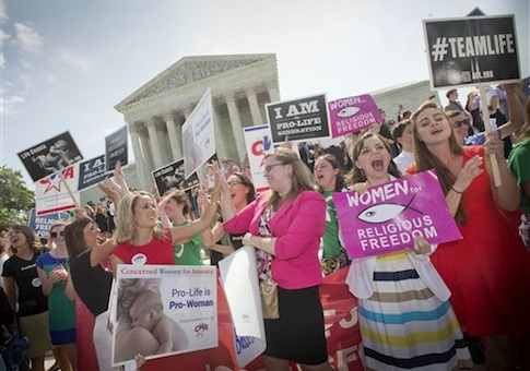 Demonstrator react to hearing the Supreme Court's decision on the Hobby Lobby case outside the Supreme Court