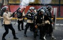 Bolivarian National Police fire tear gas toward opposition demonstrators in Caracas, Venezuela. / AP