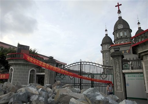 In this photo taken July 16, 2014, a church member of Zengshan Village Christian Church stands near rocks piled up in front of the gate to prevent government workers from moving in equipment to demolish the cross