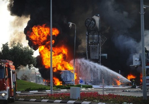 An Israeli firefighter tries to extinguish a petrol station on fire after it was hit by a rocket fired from Gaza in Ashdod, Israel, Friday, July 11