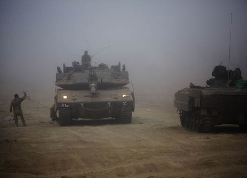 An Israeli tank moves through the morning mist near the Israel and Gaza border / AP