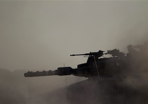 An Israeli tank takes a position along the Israel-Gaza Border