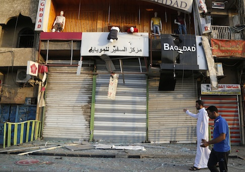 Residents inspect the site of bomb attack at a market in Baghdad's Sadr City