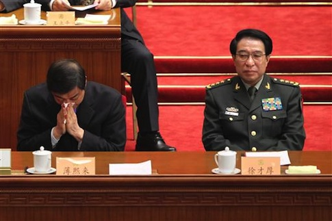 Bo Xilai, left, then Secretary of the Chongqing Municipal Committee of the Communist Party of China (CPC) and son of former Chinese Vice Premier Bo Yibo, blows his nose next to general Xu Caihou, then Vice Chairman of the Central Military Commission of China