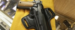 A semi-automatic handgun and a holster are displayed at a North Little Rock, Ark., gun shop
