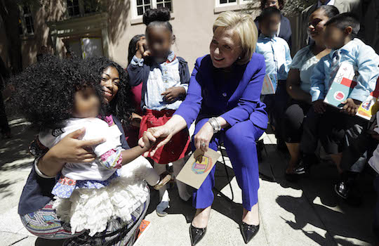 Hillary Clinton (seated, obviously) attempts to play with a frightened child. (AP)