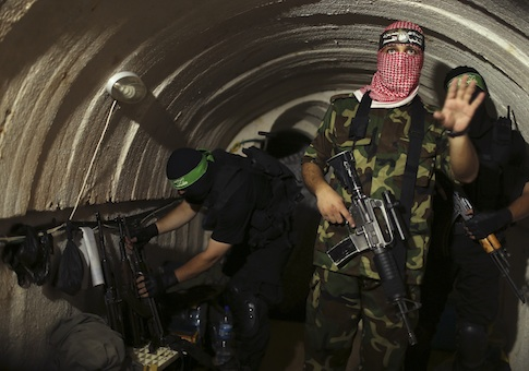 A Palestinian fighter from the Izz el-Deen al-Qassam Brigades, the armed wing of the Hamas movement, gestures inside an underground tunnel in Gaza August 18