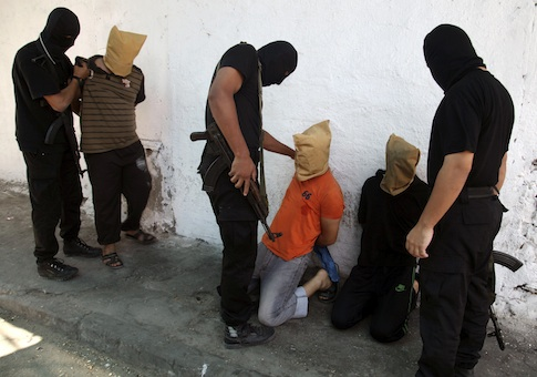 Hamas militants grab Palestinians suspected of collaborating with Israel, before executing them in Gaza City August 22