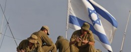 Israeli soldiers, backdropped by the national flag, sit on their armored personnel carrier as they clean their weapons
