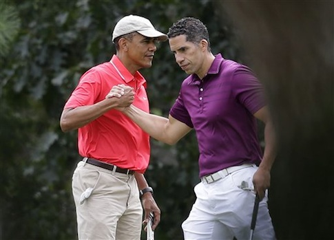President Barack Obama, left, shakes hands with Cyrus Walker, cousin of White House senior adviser Valerie Jarrett, while golfing at Farm Neck Golf Club in Oak Bluffs, Mass., on the island of Martha's Vineyard