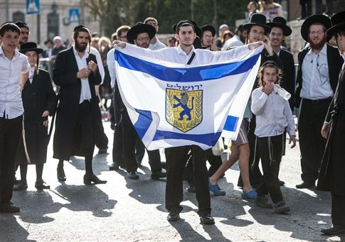 An ultra orthodox Jewish man holds a flag with the symbol of the Jerusalem monicipality, at the scene of the digger attack. One man was killed and six other were wounded as a 19 year-old Palestinian man driving a digger, went on a rampage in the center of Jerusalem.